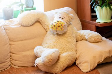 Big children's toy bear of vanilla color in yellow medical mask is sitting sprawled on sofa and looking at camera. Self-isolation during coronavirus pandemic concept. Stay at home. Light overlay.