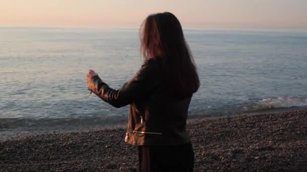 Dívka přijde na okraj moře a hodí kamínky do vody.