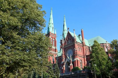 Famous gothic red church historic architecture landmark in Helsinki, Finland with blue sky and vivid green grass. City Europe travel photography
