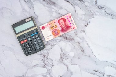 Finance Business concept. Pile of Chinese Yuan RMB bank notes, and calculator on table.