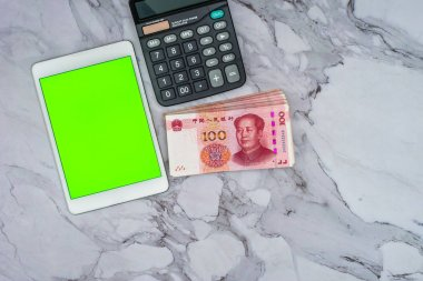 Finance Business concept. Pile of Chinese Yuan RMB bank notes, green screen touchscreen tablet and calculator on table.