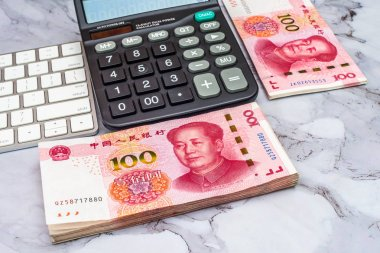 Finance Business concept. Pile of China Chinese Yuan RMB bank notes, calculator and keyboard on table.
