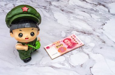 A pile of China Chinese 100 dollar bank notes, and a piggy bank figurine