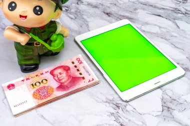 Finance Business concept. China Chinese Yuan RMB bank notes, and green screen touchscreen tablet on table.