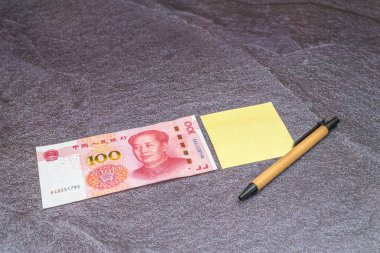 Finance Business concept. One China Chinese Yuan RMB bank note, and a yellow sticky note with pen on table.
