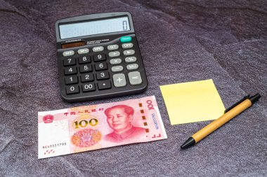 Finance Business concept. One China Chinese Yuan RMB bank note, yellow sticky note and calculator on table.