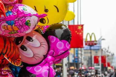 Cartoon characters balloons on sale by the street. Background blurred is China flag and McDonald's logo.