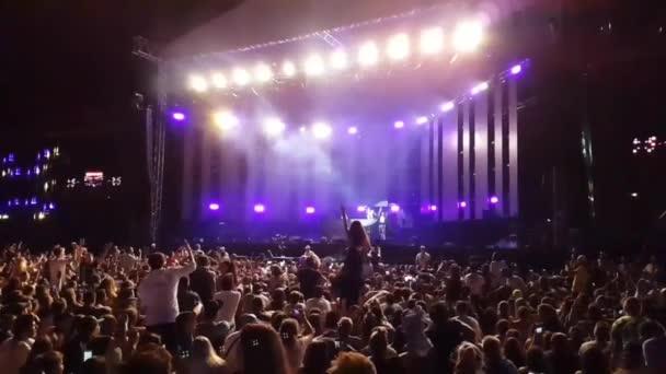 Velký vzrušený šťastný zuřící lidé dav skákání vysoko ve zpomaleném filmu na jasném světle open air stage koncert rocková skupina koncert
