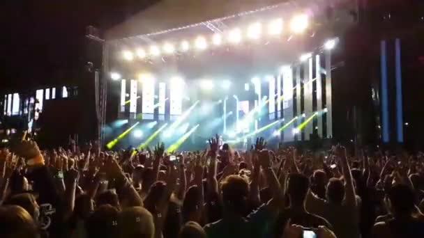 Velký šťastný vzrušený zuřiví lidé dav skákání vysoko ve zpomaleném filmu na jasné světlo open air stage koncert rocková skupina koncert