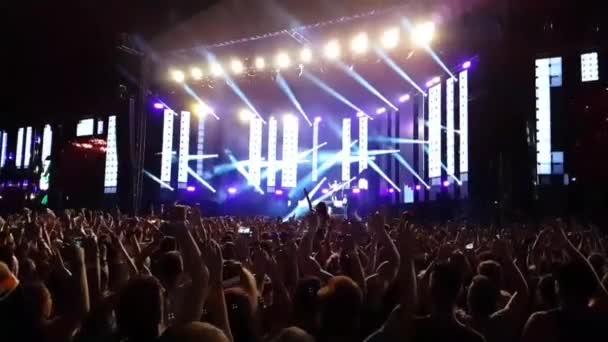Velký vzrušený zvědaví šťastní lidé dav skákání vysoko ve zpomaleném filmu na jasné světlo open air stage koncert rocková skupina koncert
