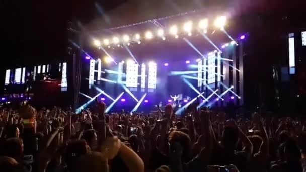Velký šťastný zvědavý vzrušený lidé dav skákání vysoko ve zpomaleném filmu na jasném světle open air stage koncert rocková skupina koncert