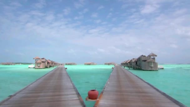 Luxury wooden bungalow hotel in turquoise ocean water paradise in steady view at Maldives island wooden bridge seascape