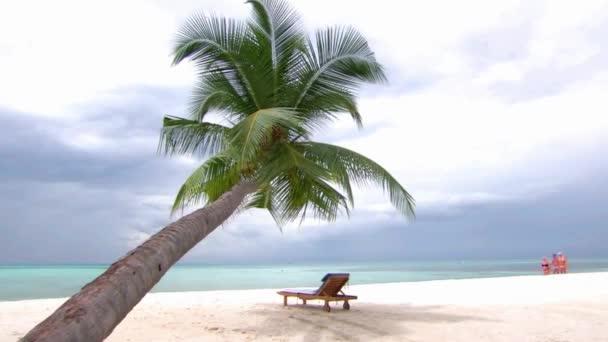 Turisté procházky u malé plážové židle pod palmami v krásném tropickém oceánu Maledivy ostrov luxusní resort seascape