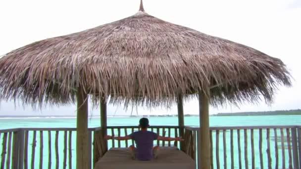 Mladý muž meditační sezení v malém bungalovu stanu s krásným výhledem na tyrkysové vody tropický oceán na Maledivách