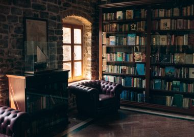 Luxury wooden library with leather armchair and bookshelves
