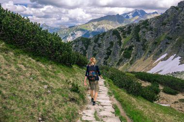 GIrl with backpack trekking on the rocky path in Tatra mountains, Poland