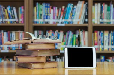 Old books in library with tablet
