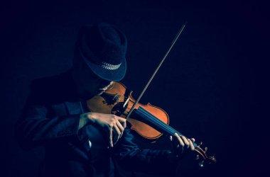Violin player in dark studio
