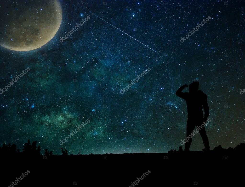 silhouette of a man  looking to the moon