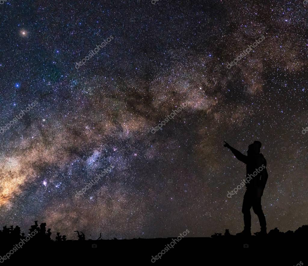 man pointing to milky way