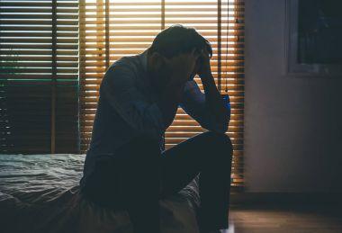 depressed man sitting on bed