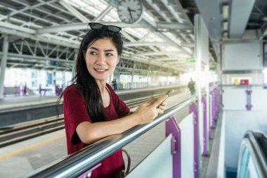 Asian woman passenger using smartphone