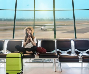 Happy Asian woman traveler holding the passport with suitcases and waiting for airplane arrive in modern an airport, travel and transportation with technology concept. stock vector