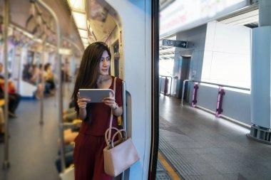 Asian woman passenger using tablet
