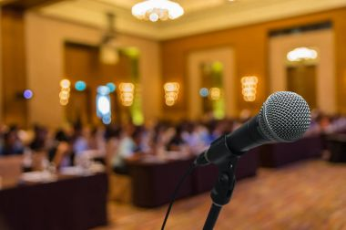 Microphone over blurred photo of conference hall