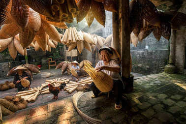 Old Vietnamese female craftsman making the traditional bamboo fish trap or weave at the old traditional house in Thu sy trade village, Hung Yen, Vietnam, traditional artist concept