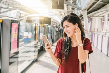Asian woman passenger with casual suit using and listening the song via smart mobile phone in the BTS Skytrain rails or MRT subway for travel in the big city
