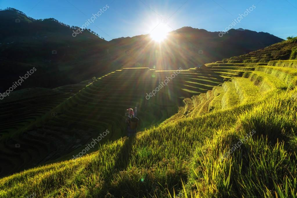 Undefined Vietnamese Hmong children pointing the dream in rice terrace when the sunset time with lens flare at mam xoi of mu cang chai district,Yenbai province, northwest of Vietnam.
