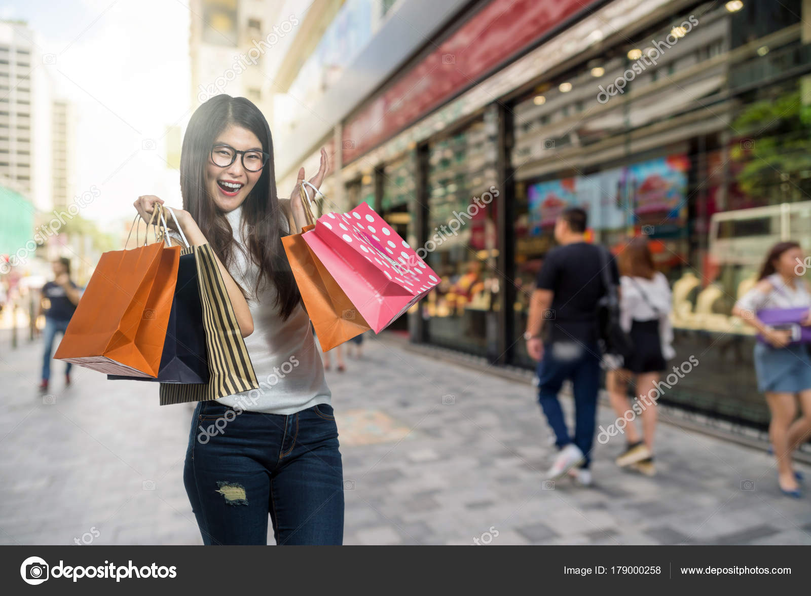 f72aecea301 Happy young asian woman shopping in happy feeling and holding the product  paper bag over Abstract blurred photo of shopping store in outdoor store  mall with ...
