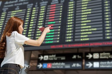 Asian woman traveler holding the passport and pointing at the flight information screen in modern an airport, lifestyle travel and transportation concept.
