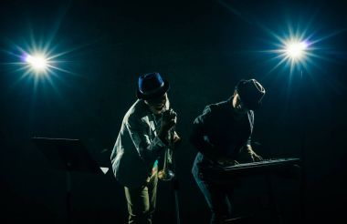 Musician Duo band playing a keyboard and singing on black background with spot light and lens flare, musical concept