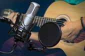 Profesionální kondenzátorový studiový mikrofon nad abstraktní fotografie rozmazané Closeup hudebník hry kytara, hudební nástroj koncept