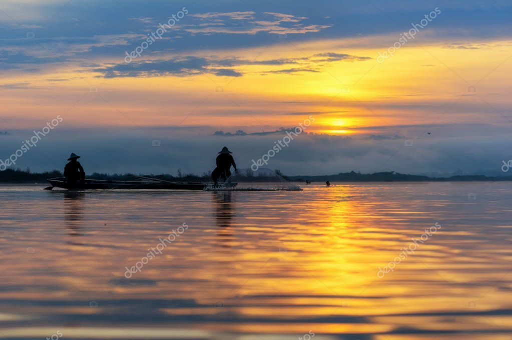 Фотообои Silhouette of asia traditional fisherman in action when fishing at sunrise in the nature river at the early morning when senrise time