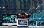 Fotografie Zadní strana sedací podnikatel, který se dívá na akciovém trhu výměna graf přes na panoráma s počítači nastavena Zobrazit pozadí grafu obchodování na stůl, obchodní technologické a obchodní koncept