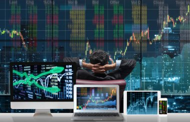 Back side of sitting businessman who is looking at stock market exchange graph over the cityscape with Computer set show Trading graph background on the table, Business technology and trading concept