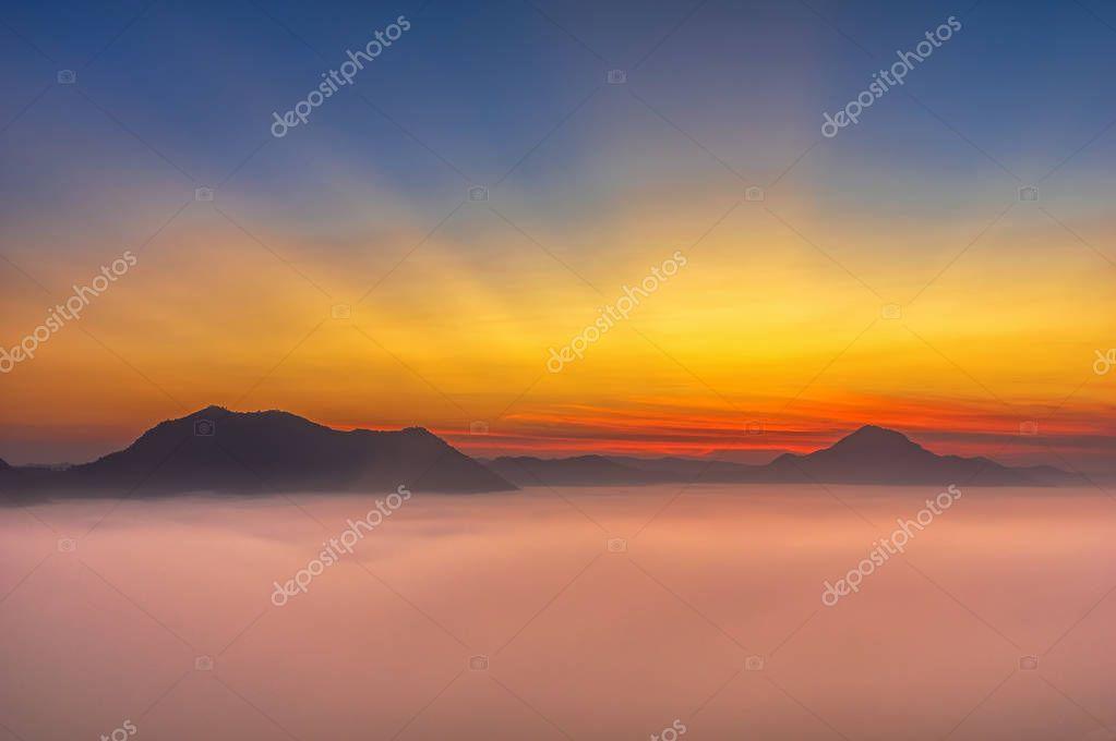 Fantastic Landscape of Misty Mountain with sun rays over Phu Thok mountain hills, Loei province, Thailand.