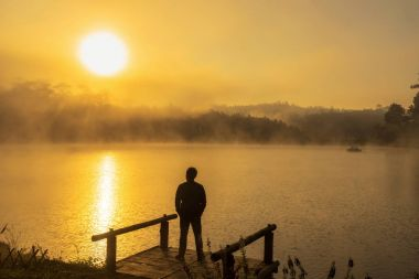 Silhouette Depressed man standing on the houseboat river lake at the sunrise time, dramatic and loneliness concept