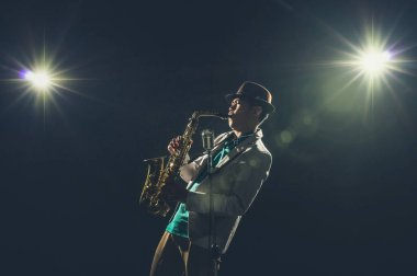 Asian Musician playing the Trumpet with spot light and lens flare on the stage, musical concept