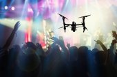 Fotografie Closeup silhouette of Drone flying for taking video of Concert crowd and Music fanclub with show hand action which follow up the songer at the front of stage, musical and concert concept