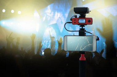 Closeup smart mobile phone taking Live of Songer hand holding the microphone and singing over Concert crowd in silhouettes of Music fanclub show hand, technology live streaming and broadcast concept