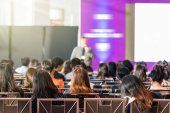 Zadní pohled na publikum v konferenční sál nebo seminář zasedání, které mají reproduktor před místností na jeviště, obchodní a vzdělávací koncepce