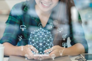 Polygonal brain shape of an artificial intelligence with various icon of smart city Internet of Things Technology over Asian businesswoman hand using the smart mobile phone,AI and business IOT concept