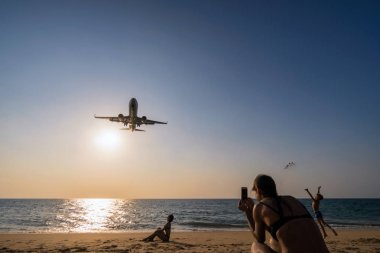 PHUKET, Thailand - FEB 5, 2018 : Undefined Travelers looking and talking photo to the Airplane landing closely at the sea beach beside the phuket international airport on Febuary 5, 2018, Thailand.