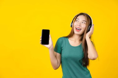 Happiness Asian smiling young woman wearing technology wireless headphones for listening the music via smart mobile phone on isolated yellow color background, Lifestyle and leisure with hobby concept