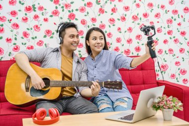 Asian Vlogger of married couple playing the music and taking video and stream live to attendee via mobile phone by social media channel, lovers and valentine, vlog and influencer freelance concept