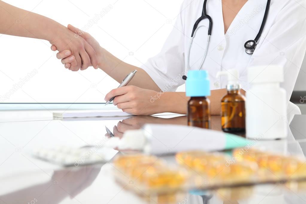 cf4a23fc07c37 Médico escreve a receita e dando um aperto de mão para sua paciente no  consultório médico com drogas na mesa — Foto de amedeoemaja